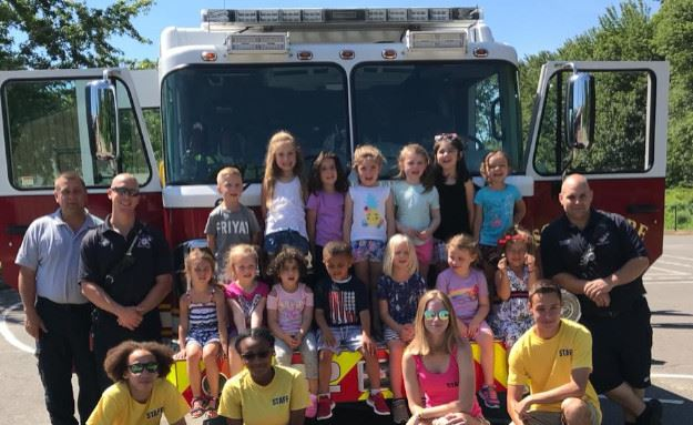 Campers, counselors and firefighters in front of a fire truck