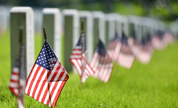 American flags in front of headstones in cemetery
