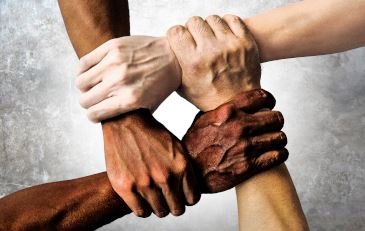 Four hands of varying skin tones holding one another